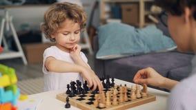 Menino esperto que joga a xadrez com as partes moventes da mãe que expressam a emoção positiva vídeos de arquivo