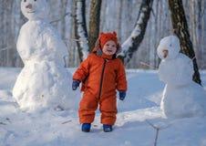 Menino europeu e o boneco de neve em uma floresta nevado fotografia de stock royalty free
