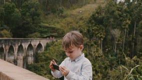 Menino europeu pequeno bonito feliz do tiro médio que toma a foto do smartphone em Ella Nine Arches Bridge em férias de Sri Lanka video estoque