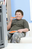 Menino excesso de peso com as varas de cenoura em Front Of Television Fotos de Stock Royalty Free