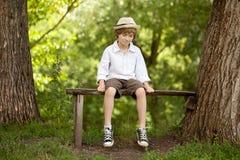 Menino Fair-haired em um chapéu, camisa, shorts imagem de stock