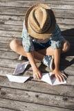 Menino fazendo os barcos de papel no cais de madeira Foto de Stock Royalty Free