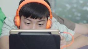 Menino feliz asiático novo à utilização na tabuleta com cara do sorriso vídeos de arquivo