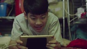 Menino feliz asiático novo à utilização na tabuleta com cara do sorriso filme