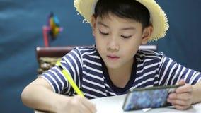 Menino feliz asiático pequeno que olha na tela do telefone celular e da pintura, com cara do sorriso video estoque