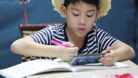 Menino feliz asiático pequeno que olha na tela do telefone celular e da pintura, com cara do sorriso filme
