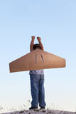 Menino feliz com as caixas de cartão das asas contra o sonho do céu da mosca imagens de stock royalty free