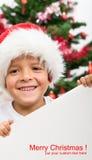 Menino feliz com chapéu do Natal e sinal em branco Imagens de Stock Royalty Free