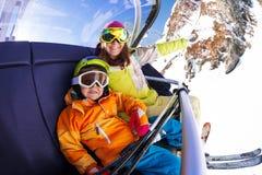 Menino feliz com a mãe no elevador de cadeira do esqui Fotografia de Stock