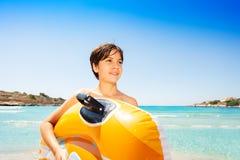 Menino feliz com o flutuador inflável na praia tropical foto de stock royalty free