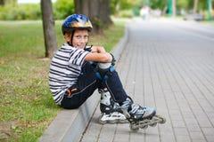 Menino feliz com patins de rolo Fotografia de Stock Royalty Free