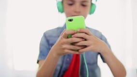 Menino feliz com smartphone e fones de ouvido em casa vídeos de arquivo