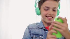 Menino feliz com smartphone e fones de ouvido em casa filme