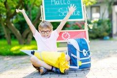 Menino feliz da criança com os vidros que sentam-se pela mesa e a trouxa ou a sacola fotos de stock