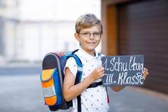 Menino feliz da criança com vidros e trouxa ou sacola Aluno na maneira à escola Criança adorável saudável Foto de Stock Royalty Free