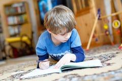 Menino feliz da criança da escola em casa que faz trabalhos de casa Fotos de Stock