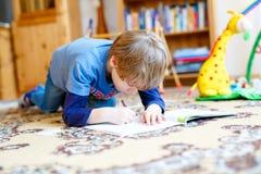 Menino feliz da criança da escola em casa que faz trabalhos de casa Foto de Stock