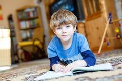 Menino feliz da criança da escola em casa que faz trabalhos de casa Foto de Stock Royalty Free