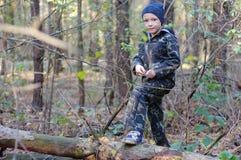Menino feliz da criança nas madeiras que procuram cogumelos O menino está vestindo um uniforme da camuflagem imagem de stock
