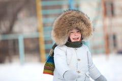 Menino feliz da criança no revestimento do inverno com guarnição da pele Foto de Stock Royalty Free