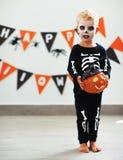 Menino feliz da criança no traje de esqueleto ao Dia das Bruxas foto de stock