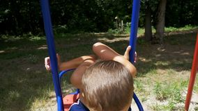 Menino feliz da criança pequena que balança em um balanço no movimento lento vídeos de arquivo