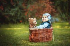 Menino feliz da criança que joga com brinquedo do urso ao sentar-se na cesta no gramado verde do outono Crianças que apreciam a a Fotografia de Stock