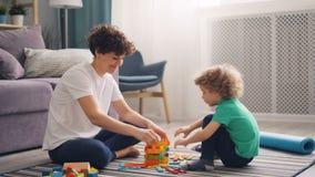 Menino feliz da criança que joga com brinquedos de madeira quando a mãe o ajudar na casa