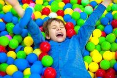 Menino feliz da criança que joga na opinião alta do campo de jogos plástico colorido das bolas Criança engraçada que tem o divert fotografia de stock royalty free