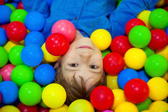 Menino feliz da criança que joga na opinião alta do campo de jogos plástico colorido das bolas Criança engraçada que tem o divert imagens de stock royalty free