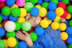 Menino feliz da criança que joga na opinião alta do campo de jogos plástico colorido das bolas Criança engraçada que tem o divert fotos de stock