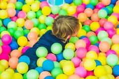 Menino feliz da criança que joga na opinião alta do campo de jogos plástico colorido das bolas Criança engraçada que tem o divert fotografia de stock