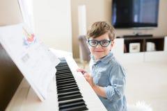 Menino feliz da criança que joga o piano fotografia de stock royalty free