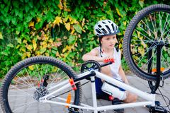 Menino feliz da crian?a pequena no capacete branco que repara sua bicicleta imagens de stock royalty free
