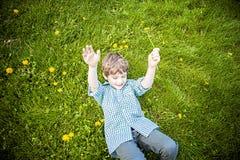 Menino feliz de sorriso que coloca na grama fora de escolher flores foto de stock royalty free