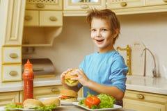 Menino feliz de sorriso que guarda Hamburger caseiros ou Imagens de Stock Royalty Free