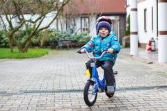 Menino feliz de três anos que montam na bicicleta no outono ou no inverno, Imagens de Stock
