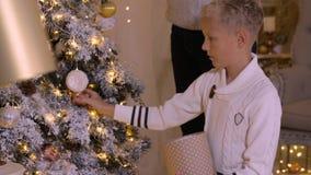 Menino feliz do adolescente que decora a árvore de Natal pelo brinquedo e pela festão de vidro na casa filme
