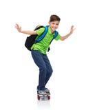 Menino feliz do estudante com trouxa e skate Imagem de Stock Royalty Free