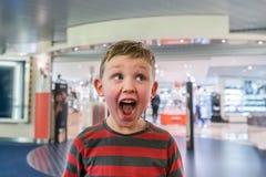 Menino feliz e entusiasmado na frente de uma loja ansiosa para ir na compra Fazendo a face engraçada Fotos de Stock