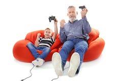 Menino feliz e seu avô com controladores do jogo de vídeo imagem de stock