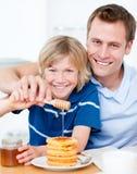 Menino feliz e seu pai que põr o mel sobre waffles Imagens de Stock
