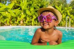 Menino feliz em óculos de sol dados forma no colchão de ar verde foto de stock royalty free