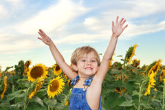 Menino feliz em um campo dos girassóis Imagens de Stock Royalty Free