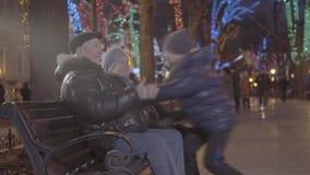 Menino feliz entusiasmado do neto que corre sobre às avós que sentam-se no banco no parque festivo da noite da atmosfera do Natal filme