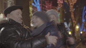Menino feliz entusiasmado do neto que corre sobre aos granparents velhos que abraçam no parque festivo acolhedor da noite do Nata video estoque
