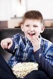 Menino feliz louro que presta atenção à tevê e que come a pipoca Imagens de Stock