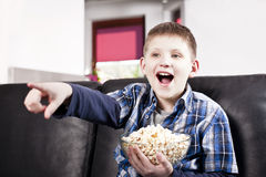 Menino feliz louro que presta atenção à tevê e que come a pipoca Fotos de Stock Royalty Free