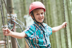 Menino feliz na aventura e na atividade de escalada do ropeway na floresta Fotografia de Stock Royalty Free