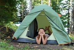 Menino feliz na barraca de acampamento Foto de Stock